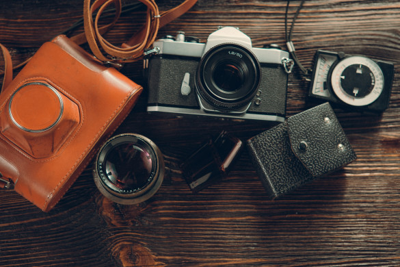 Old film camera, lenses and old exposure meter on a wooden background